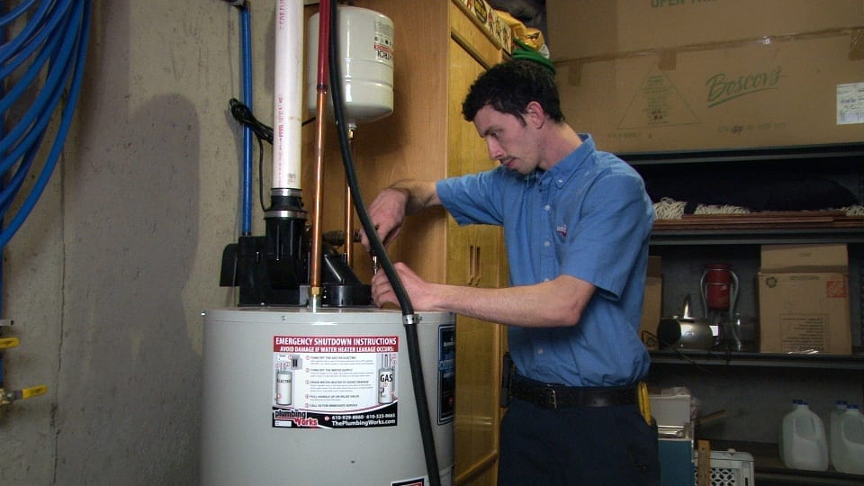heating plumbing technician repairs home water heater