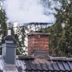 Smoking chimney and pipe on the top of a house in rural area