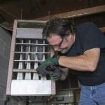 Technician checking out a overhead gas furnace in a commercial building.