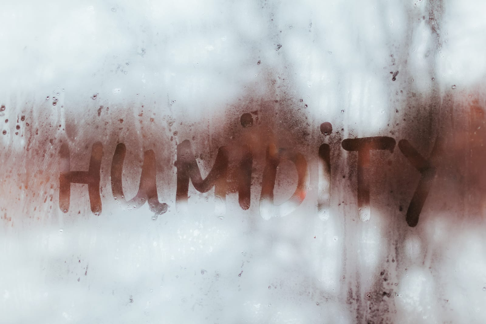 Humidity word written on wet window. High level of dampness in apartment.