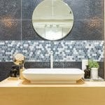 A vessel sink sits on a tan countertop in a bathroom with a circular mirror on the wall.