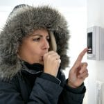 woman with warm clothes on feeling cold and adjusting thermostat